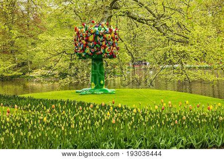 Lisse, Holland - May 23, 2017: Park Keukenhof - flower garden, Holland. Artificial tree decorated birds