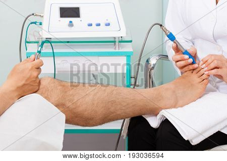 Doctor using electro acupuncture equipment for diagnostic