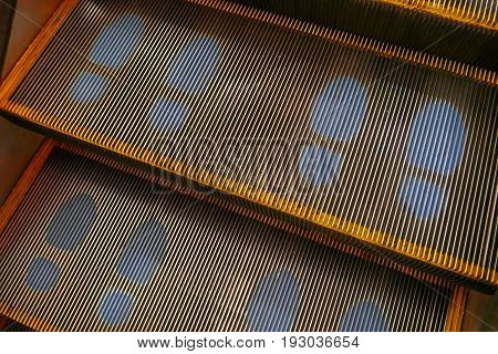 escalator with blue footprint screen on step
