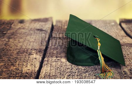 green high school graduation hat on wooden