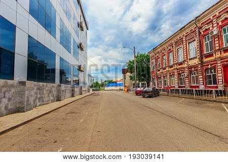 Architecture of the 19th century and century 21. Houses stand from two sides of the road. The old building is put from a brick with elements of a figured laying. New of glass and concrete. Armavir.