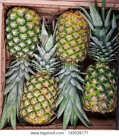 Fresh pineapples stacked in a carton from market