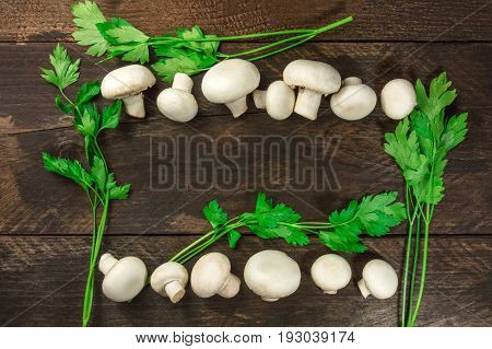 An overhead photo of fresh white mushrooms with green parsley, forming a frame on a dark rustic texture with a place for text
