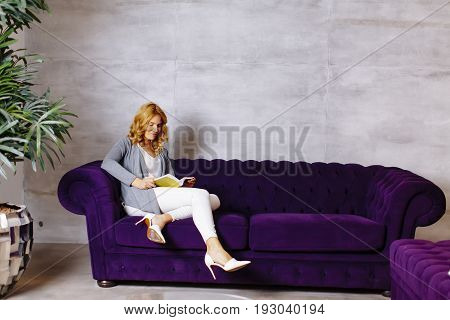 Young Woman Reading Storybook On Couch At Home