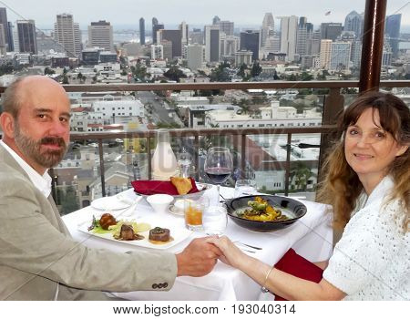 SAN DIEGO, CALIFORNIA, JUNE 9. Mr. A's on June 9, 2017, in San Diego, California. A Middle Aged Couple Dine Overlooking the Downtown San Diego Cityscape from Mr. A's Restaurant.