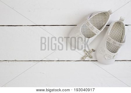Christening background with white baby booties and crystal cross isolated on white plank floor