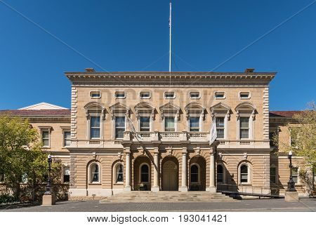 Hobart Australia - March 19. 2017: Tasmania. The beige rectangular facade of historic Town Hall under blue sky. Some green trees on side. White flag mast on top.