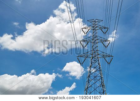 High voltage pole and transmission line against blue sky and clouds background. High voltage tower.