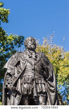 Hobart Australia - March 19. 2017: Tasmania. Bust of bronze statue of King Edward VII shows him looking proudly and defiant. Green park background and blue sky.