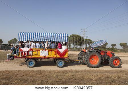 El Rocio Spain - June 1 2017: Pilgrims in a tractor drawn trailer on the road to El Rocio during the pilgrimage Romeria 2017. Province of Huelva Almonte Spain