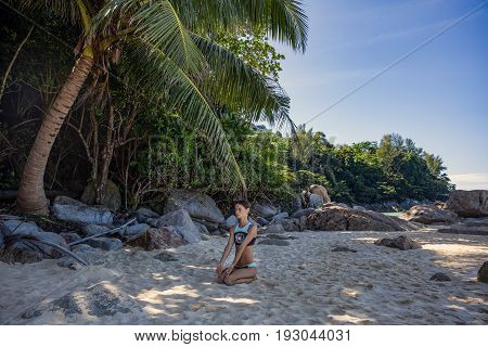 Young woman with dreadlocks doing yoga sitting amongst the palm trees
