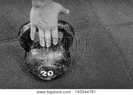 Hand taking old and rusty kettle bell from the gym floor. Selective focus, indoor light, black and white.