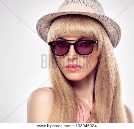 Fashion Portrait Beauty Sensual Blond Woman in Stylish Sunglasses. Shiny Silky Straight hair, fashion Makeup. Trendy Bang Hairstyle. Glamour Sexy Model Girl in Luxury fashion Summer Hat. Face Closeup