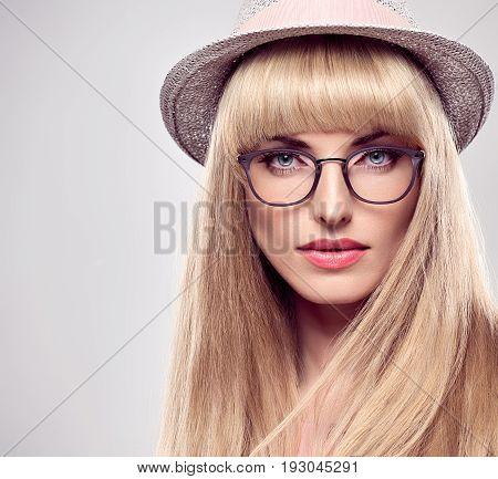 Fashion Portrait Beauty Sensual Blond Woman in Stylish glasses. Shiny straight hair, fashion Makeup, Blue Eyes. Trendy Bang Hairstyle. Glamour Sexy Model Girl in Luxury fashion Summer Hat.Face Closeup