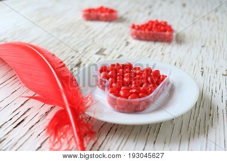 Red cinnamon hearts displayed in heart shaped containers and a red feather.