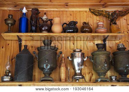 Antique samovars on a shelf on a wooden background.