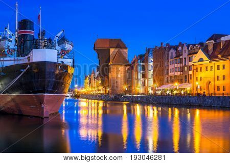 Historic port crane and ship over Motlawa river in Gdansk at night, Poland