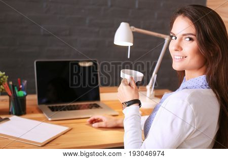 Portrait of relaxed young woman sitting at her desk holding cup of coffee. Business Woman. Workplace