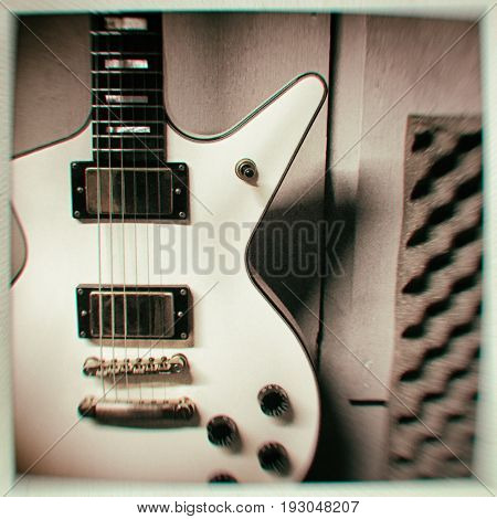 Filtered closeup of an electric guitar hanging on a wall with soundproofing foam