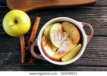 Tureen with pieces of fresh apple, sugar powder and cinnamon on dark wooden table