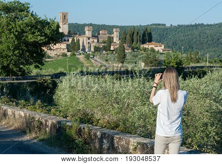 A young woman takes a picture of the historic abbey of San Michele Arcangelo Passignano in the comune Tavarnelle Val di Pesa Province of Florence Italy