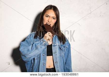 Picture of young angry hipster woman standing over gray background eating chocolate. Looking camera.