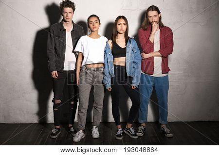 Picture of serious young hipsters friends standing over gray background. Looking camera.