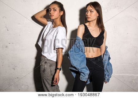 Picture of concentrated young hipsters ladies standing over gray background.