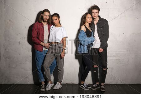 Image of young serious hipsters loving couples standing over gray background.