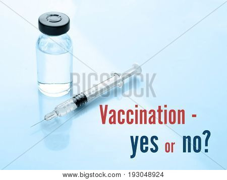 Vaccination debate concept. Vial and syringe with vaccine on blue background