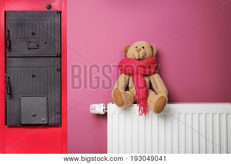 Energy savings concept. Solid fuel boiler and radiator with toy bear on color background