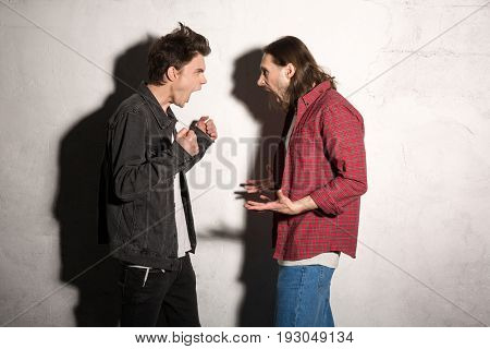 Image of screaming angry young hipsters men standing over gray background.