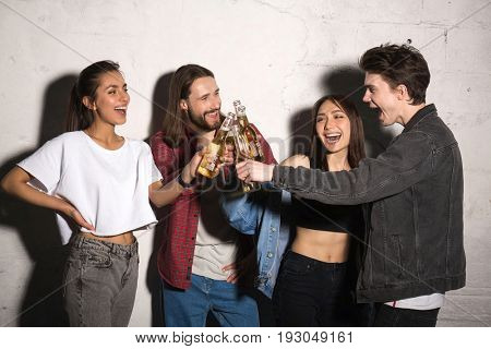Image of young hipsters friends standing over gray background drinking beer.
