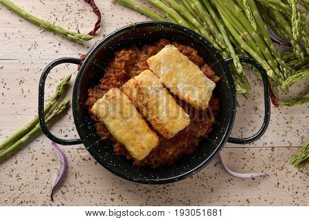 high-angle shot of a frying pan with bacalao a la vizcaina, a typical spanish recipe of codfish, with a tomato sauce with garlic, onion and red pepper, on a rustic wooden table