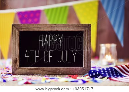 a wooden-framed chalkboard with the text happy 4th of july written in it and an American flag, placed on a rustic wooden background sprinkled with confetti and a colorful garland in the background