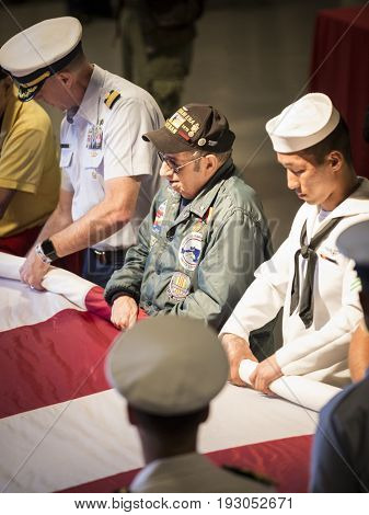 Active U.S. military service members alongside retired veterans unfurl a large American Flag at the Memorial Day ceremony on the Intrepid Sea, Air & Space Museum, Fleet Week, NEW YORK MAY 29 2017.