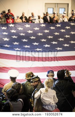 Active U.S. military service members alongside retired veterans hold a large American Flag at the Memorial Day ceremony on the Intrepid Sea, Air & Space Museum, Fleet Week, NEW YORK MAY 29 2017.