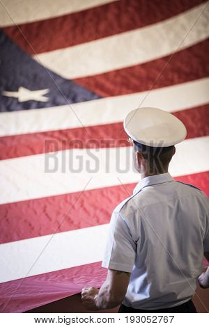 U.S. Coast Guard military service member holds a large American Flag during the Memorial Day Observance ceremony on the Intrepid Sea, Air & Space Museum, Fleet Week, NEW YORK MAY 29 2017.