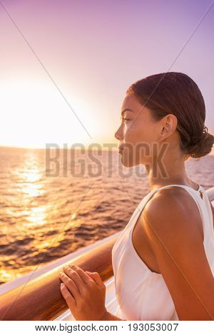 Cruise luxury travel woman Europe destination vacation holiday. Girl enjoying sunset view in elegant white evening dress from balcony suite deck. Asian beauty relaxing.