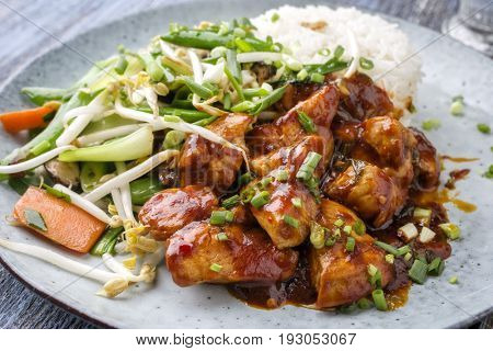 Chicken sweet-sour with Vegetable and white Rice as close-up on a plate