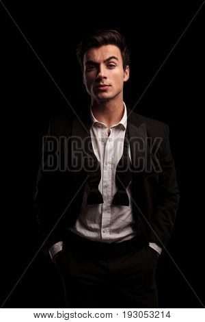 elegant man in tuxedo and undone bowtie standing with hands in pockets  on black studio background