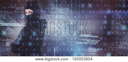 Portrait of female hacker standing wearing hoodie and balaclava against dark room