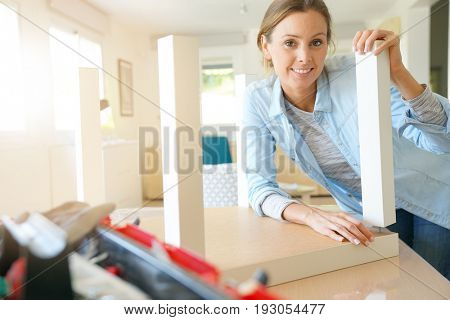 Woman doing DIY work, assembling furniture at home