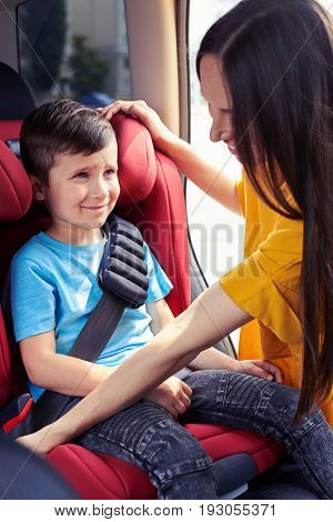 Vertical of good mom fastening seat belt of son sitting in baby sit