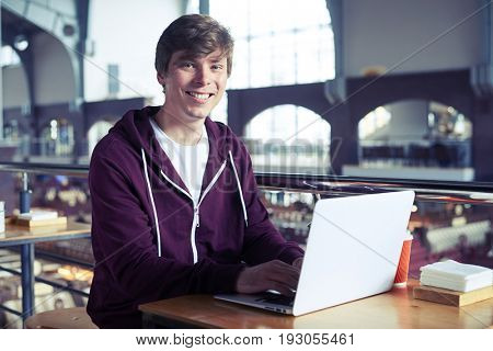 Wide shot of nice male smiling while surfing in laptop while sitting in cafe with copy space