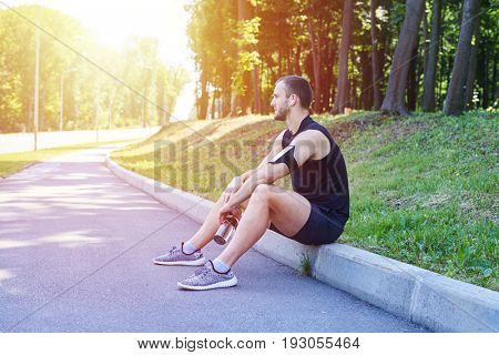 Mid shot a male wearing sport clothing, sitting on street curb, holding a bottle of water, sunny day