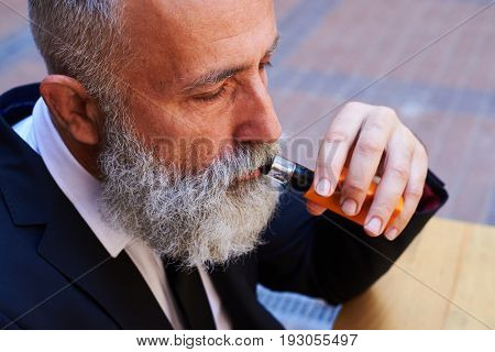 Close-up of sir with poker face smoking electrocigarette while sitting