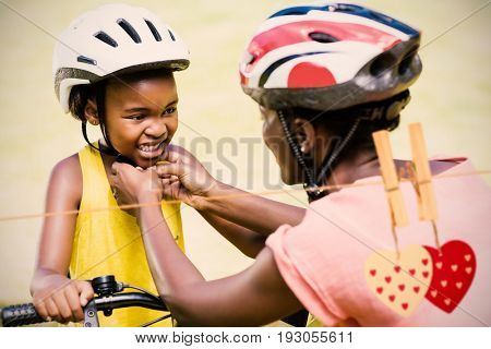 Hearts on line against mother clasping her daughters bicycle helmet