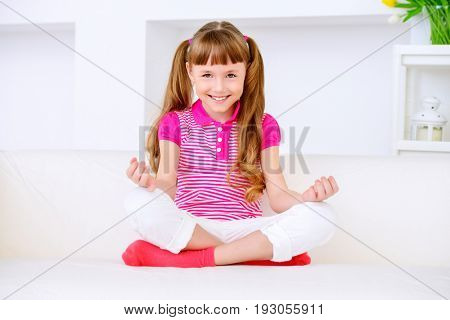 Joyful smiling child girl sitting on a sofa and having a rest at home. Happy childhood.