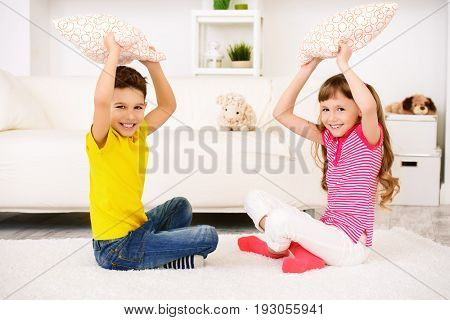 Two happy children at home. Brother and sister together. Pillow fights. Family concept.